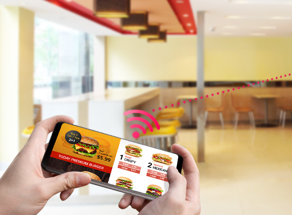A smartphone with a burger restaurant ad on screen