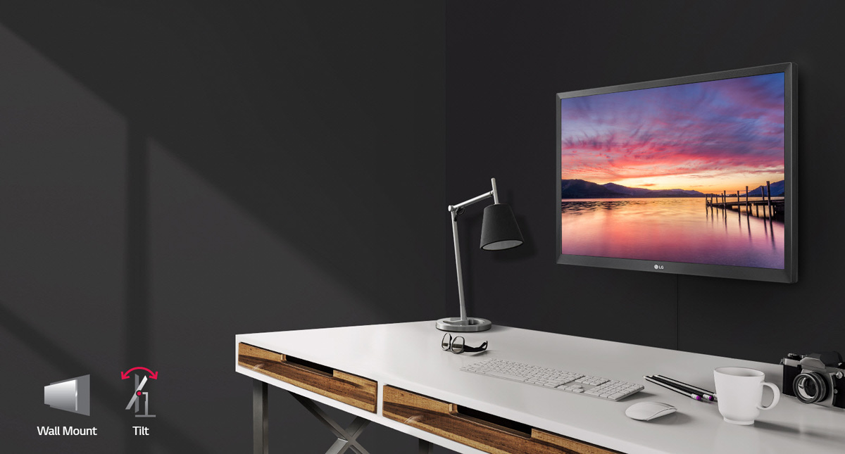 LG 27BK430H-B Monitor Wall Mounted Angled to the Left in Front of a Desk that has a lamp, glasses, keyboard, mouse, pencils, coffe mug and camera. At the bottom left of this image is a wall mount and tilt icon