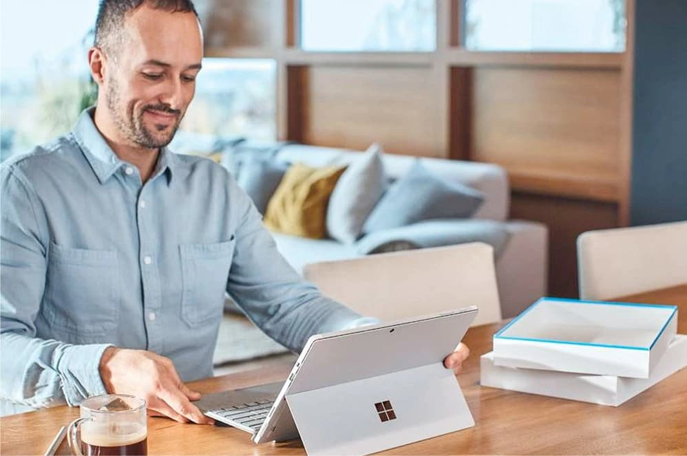 a man happily using his Surface Pro placed on a wooden desk