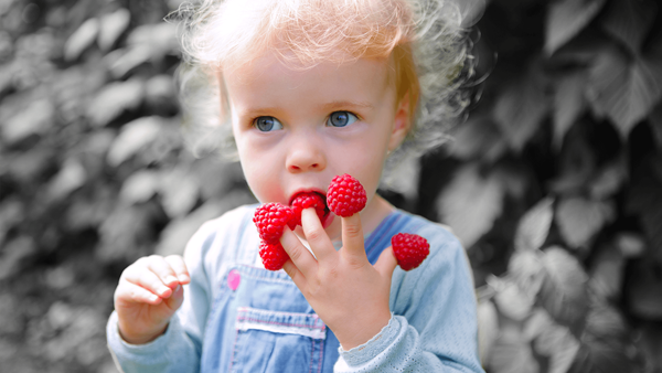 A girl has a red berry on each of her fingers with black background