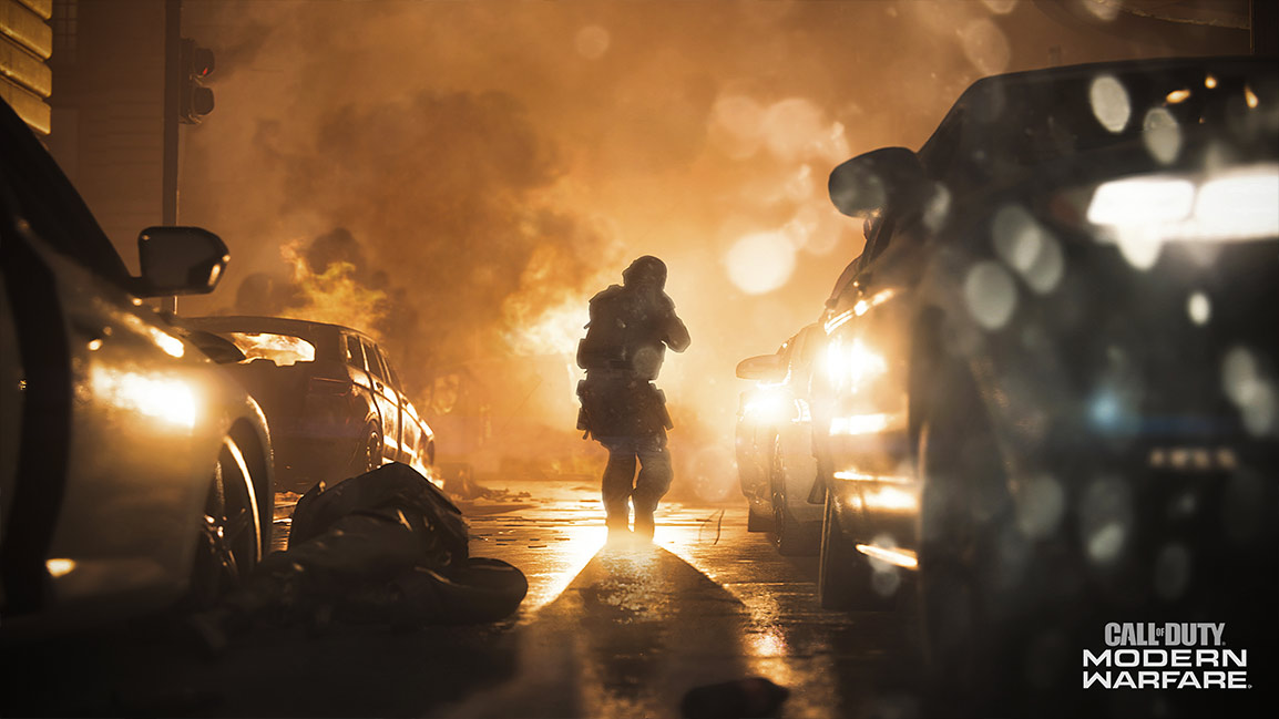 Call of Duty Modern Warfare screenshot showing a soldier approaching a fire through a city street with abandoned cars on both sides