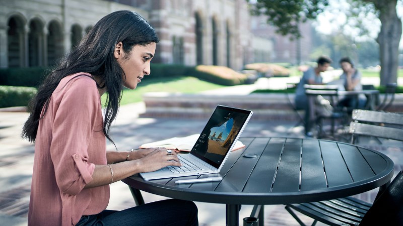 a woman typing on Surface Book placed on a desk outdoors