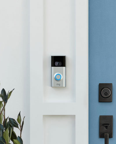 A Ring video doorbell mounted on the wall, next to a blue door