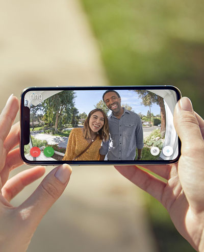 A phone in horizontal orientation held by two hands, with screen showing a live view in which there is a male and female with smile on their faces