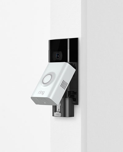 A Ring video doorbell with faceplate opened, revealing internal battery