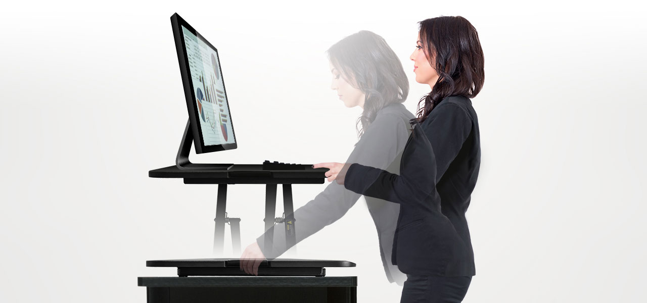 A lady who is using  the Adjustable Standing Desk Riser Monitor Stand to improve she can adjust to comfort levels