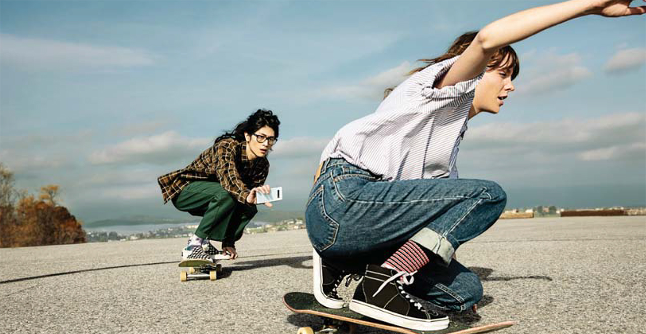 Two females skateboarding low with their knees bent. One is in front of the other and the female skater in the back is using the Samsung Galaxy S10 in her left hand to film the female skater in front of her