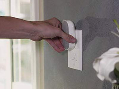 A hand plugging in the Arlo Chime to a home outlet