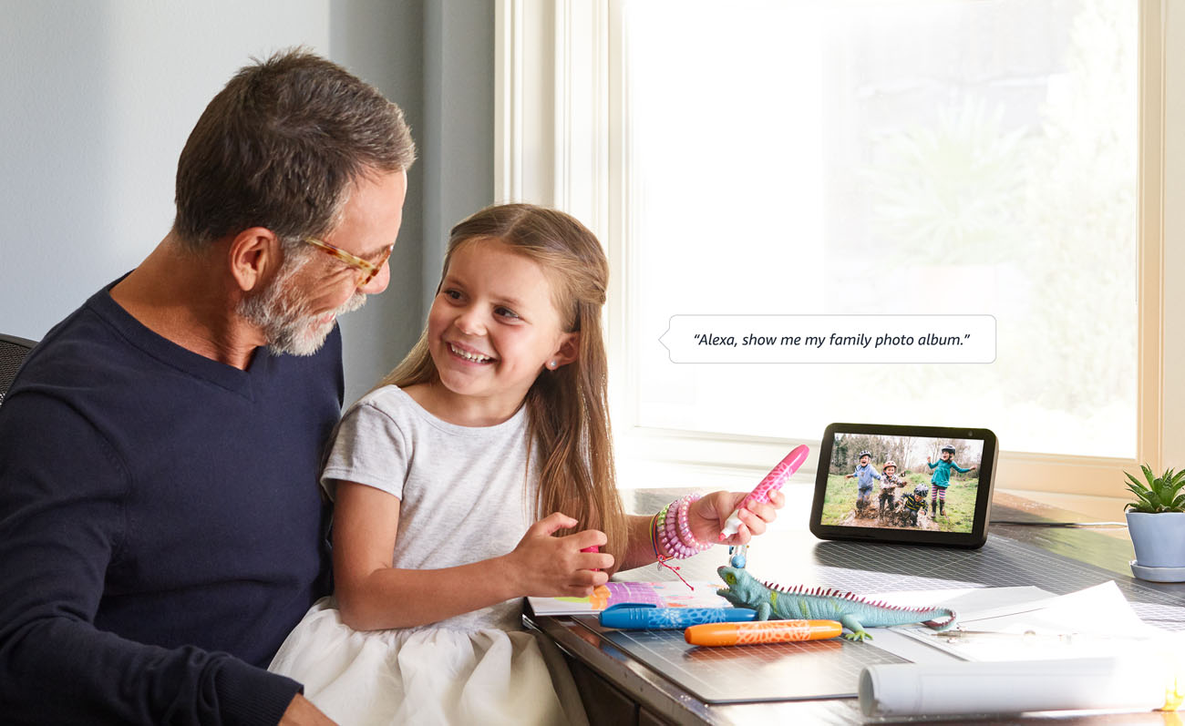 a man and his daughter sitting in front of a desk is using Echo Show 8