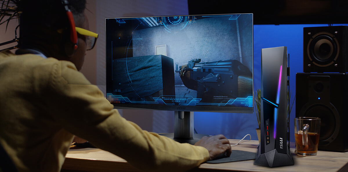 A man is gaming. The thin desktop pc next to monitor that saves spaces.