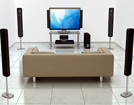 a surround sound system with a TV and a brown sofa