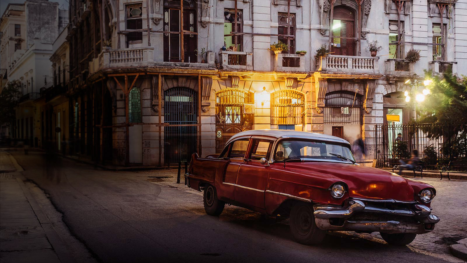 A classic car next to an old European residential city area