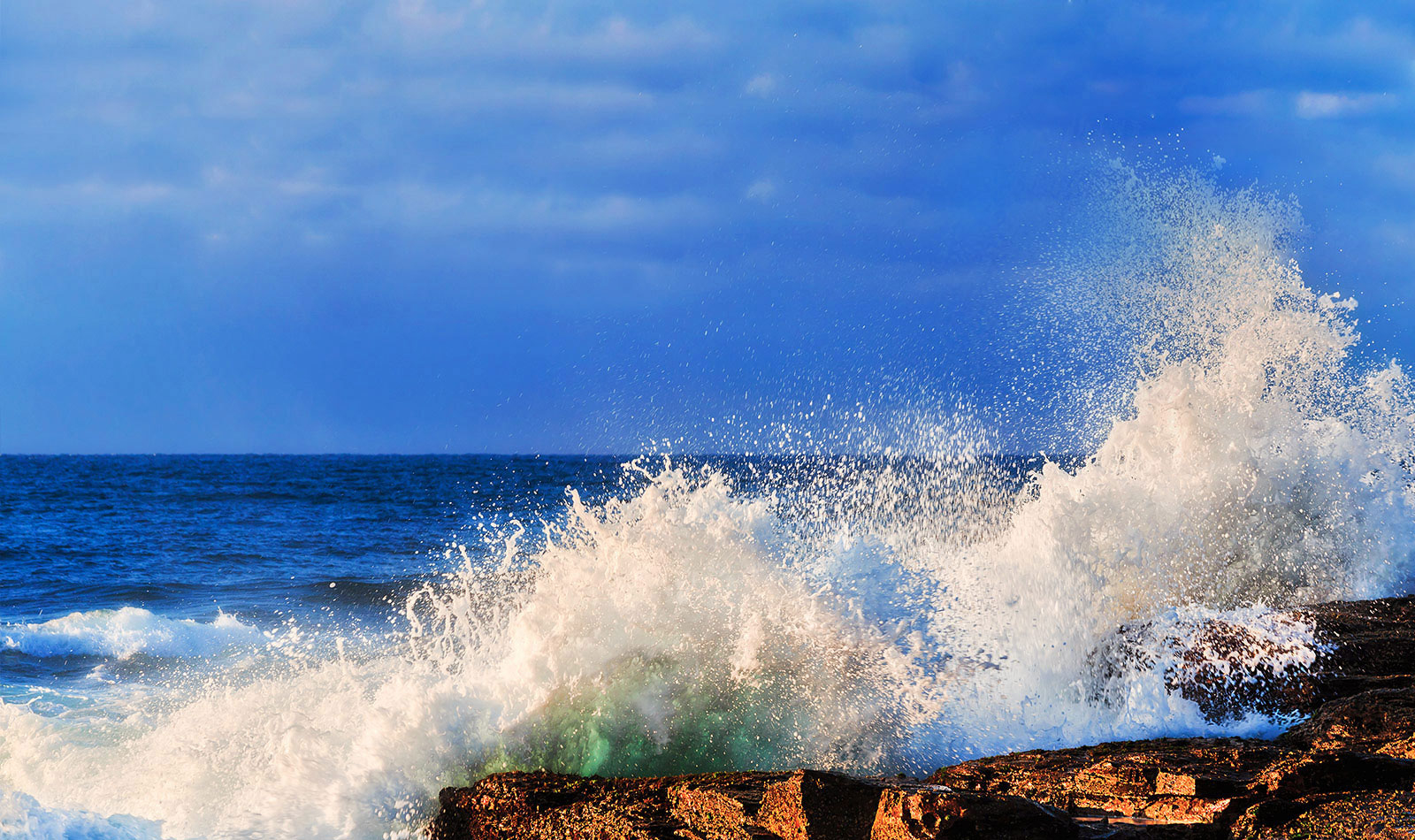 Waves from the ocean crashing onto rocks