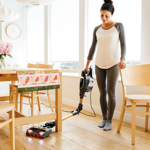 A woman utilizing the multiflex function as she has the vacuum completely under a table on a hardware floor