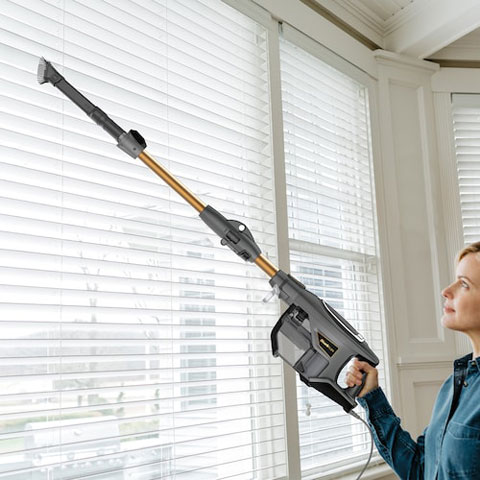 Woman using the vacuums extender to vacuum the individual shades of her window blinds