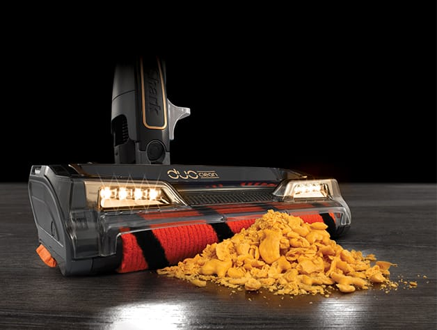 closeup of the shark HV392 pickup up crumbled cheese cracker snacks on a brown hardwood floor