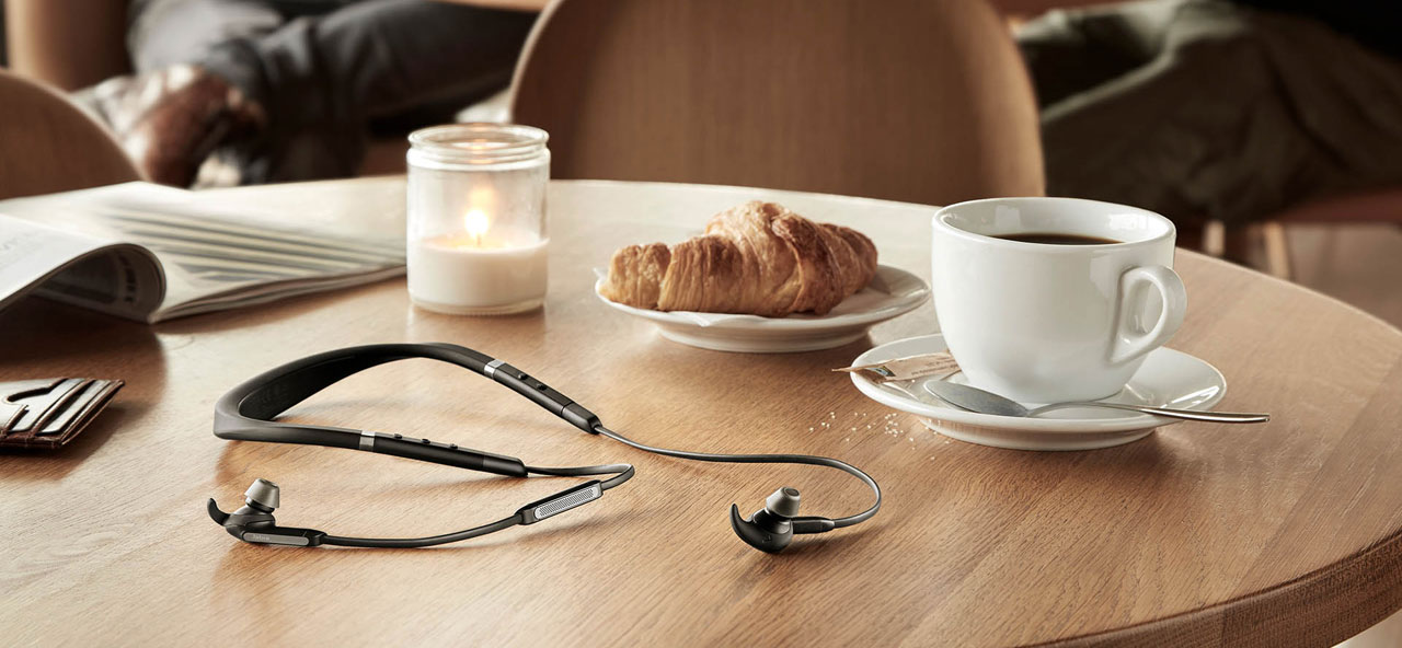 The Jabra Elite 65e on display on a dinner table, with a magazine, a cup of coffee, a plate with bread, and a bottled candle on the table