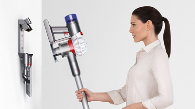 a woman is putting Dyson V7 Animal into the docking station