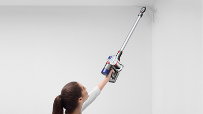 a woman lifting Dyson V7 Animal to cleaning the ceiling