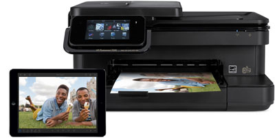 A printer outputting a photo, and in front of it is an iPad Air with its screen showing the printed photo