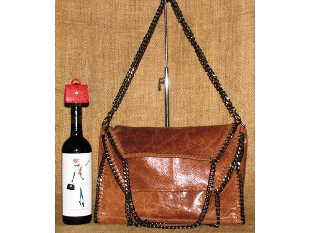 Supple, glossy, and textured genuine Italian leather bag in brown. Foldover top. Gunmetal-tone hardware. Made in Italy.