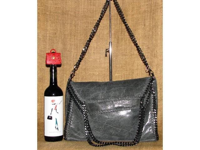 Supple, glossy, and textured genuine leather bag in grey. Foldover top. Gunmetal-tone hardware.