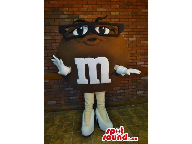 Brown M&M'S Character Canadian SpotSound Mascot Dressed In Glasses And High Heels