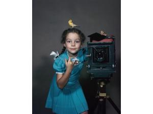Portrait of a girl standing near a camera with a canary on her head Poster Print (24 x 36)