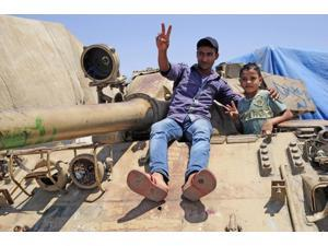 A T-55 tank with two children playing on it in Benghazi, Libya Poster Print (17 x 11)